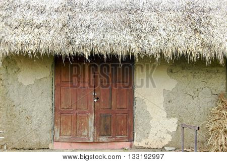close up one pannel of old soil house building and straw roof of rural life Thailand