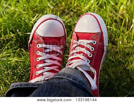 Feet in dirty red sneakers outdoors. Making first step.