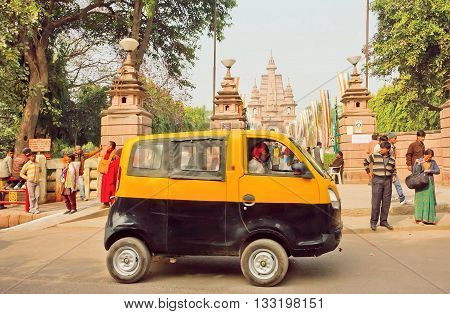SARNATH, INDIA - JAN 5, 2016: Yellow and black taxi cab driving past ancient Buddhist temple Mulagandhakuti Vihara on January 5, 2016. Sarnath is where Gautama Buddha first taught the Dharma at 500 BC.