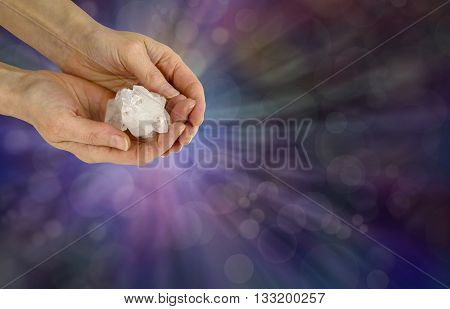 Holding a Reiki Master Apophyllite Crystal Cluster  - female crystal healer holding a Reiki Master Apophyllite Crystal Cluster on a wide purple bokeh background with copy space poster