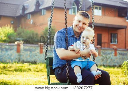 father with baby on her knees in the park sitting on a swing and smile