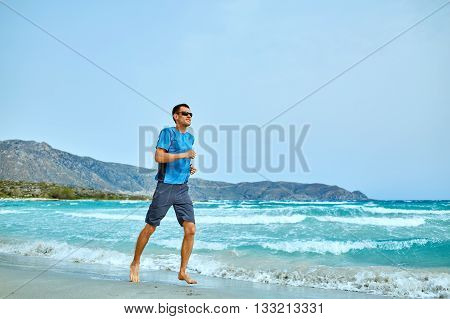 strong athletic man running on the beach along the sea front
