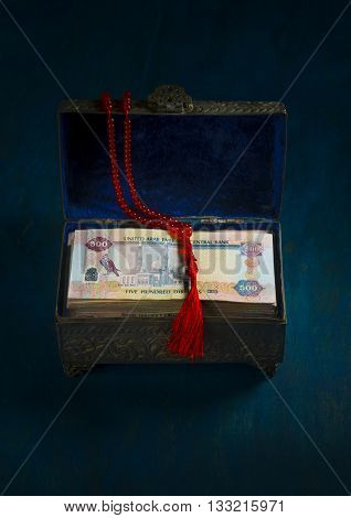 UAE Dirham currency in a vintage box and prayer beads. Front view. 'Ramadan Charity' - Conceptual image.