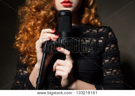 Close-up of unrecognizable red-haired woman singing in black mic