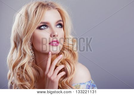 Beauty girl model withmake-up . Portrait of an attractive young woman with blond hair on a light background . Beautiful female face with clean fresh skin .