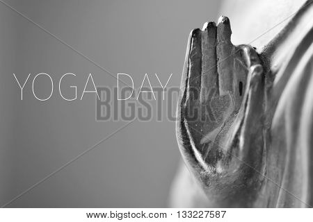 detail of a representation of the Buddha with his hand in gyan mudra in duotone and the text yoga day
