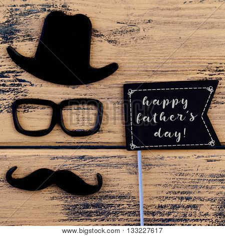 a black flag-shaped signboard with the text happy fathers day and a mustache, a pair of eyeglasses and a hat forming the face of a man, on a rustic wooden surface
