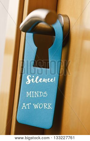 closeup of a blue door hanger with the text do not disturb hanging on the handle of a pinewood door
