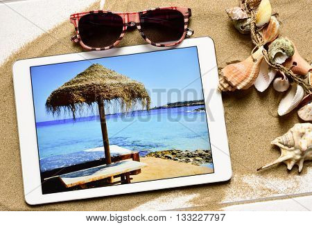 high-angle shot of a white wooden surface full of sand and an ornament made with different conchs and seashells, a pair of sunglasses and a tablet computer with the picture of a beach taken by myself