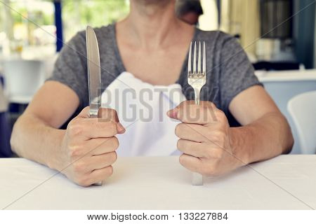 closeup of a young caucasian man sitting at a table waiting for the food, with a knife in one hand and a fork in the other hand