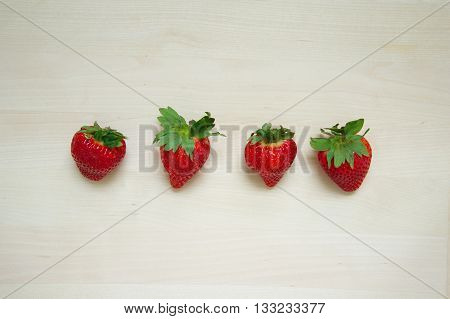 four strawberry with green leave on wood background