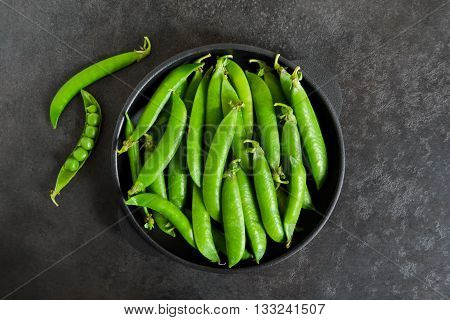 Green young peas in a cast-iron plate on a black background