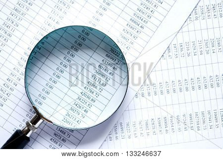 Business research. Closeup of magnifying glass on paper with digits