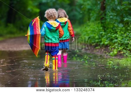 Little boy and girl play in rainy summer park. Children with colorful rainbow umbrella waterproof boots jump in puddle and mud in the rain. Kids walk in autumn shower. Outdoor fun by any weather
