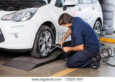 Mechanic Repairing Car Tire At Garage