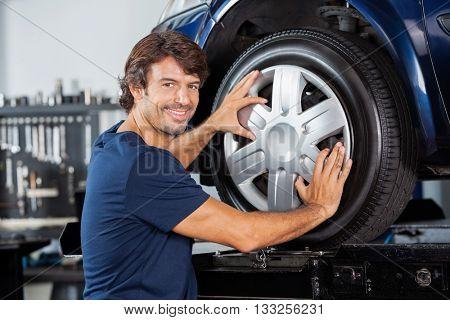 Happy Mechanic Fixing Alloy To Car Tire