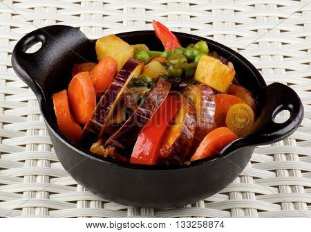 Delicious Homemade Colorful Vegetables Ragout with Striped Eggplant Carrots Potatoes Leek Red Bell Pepper and Green Pea in Black Iron Stewpot closeup on Wicker background