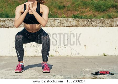 Slim Girl In Sportswear Doing Sit-ups Outdoors In The Morning