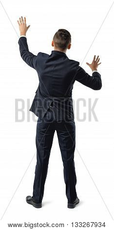 Back view of businessman touching big sensor panel or wall. Obstacles and barriers. Office clothes. Dress code. Confusion and doubt. Search exit. Pantomime.