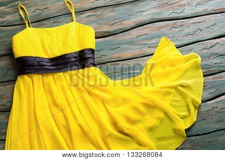 Yellow summer dress. Casual dress with black insert. Lady's garment on green shelf. Clothing item for young girls.