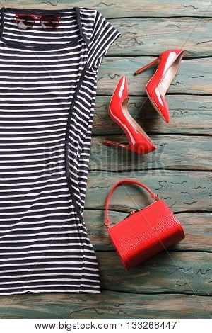 Striped dress with short sleeves. Red heel shoes and bag. Accessories and clothes on table. New items in stock.