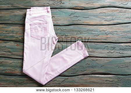 Light pink trousers. Girl's casual spring pants. Green shelf with clothing item. Merchandise sold at auction.
