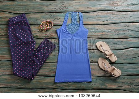 Navy pants and tank top. Sandals and dotted trousers. Lady's spring outfit and accessories. Set of small colorful bracelets.