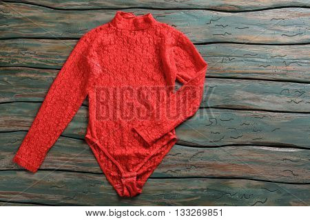 Red bodysuit top. Colorful top with long sleeves. Garment lying on green table. Discounted merchandise in local store.