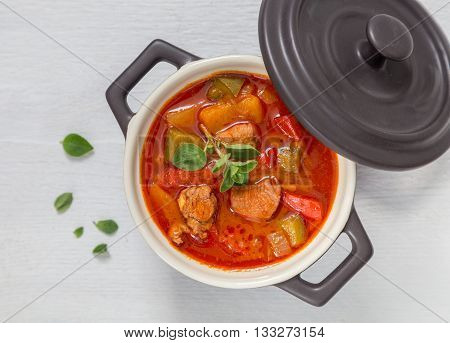 Goulash In A Black Cocotte With Marjoram On White Wood