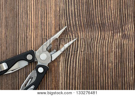 Simple pliers and multitool on wooden surface. Improved construction tools. Everyday instruments and tools. Progress. Construction and Repair.