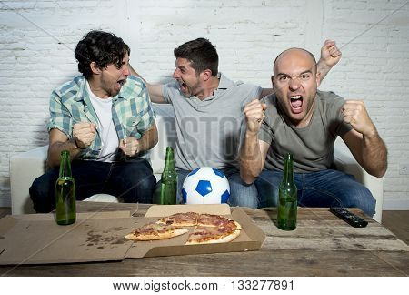 group of friends fanatic football fans watching soccer game on television celebrating goal on couch screaming excited and ecstatic in crazy happy face expression with beer and pizza