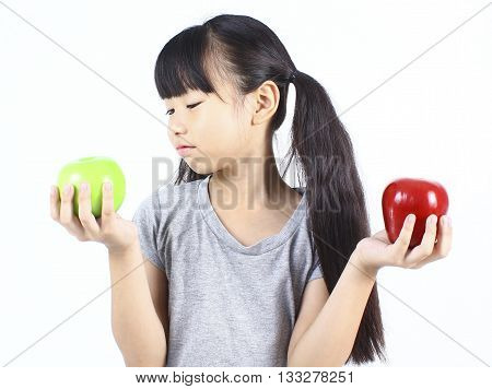 Young girl holding red and green apple.