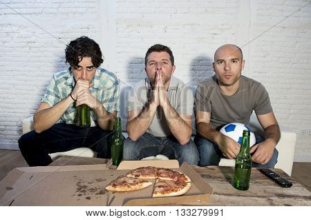 group of friends fanatic football fans watching soccer game on television with beer bottles and pizza suffering stress and crazy nervous on couch concentrated and focused