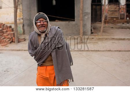 UTTAR PRADESH, INDIA - JAN 27, 2013: Poor senior man in glasses with no teeth goes on the street on January 27, 2013 in Ayodhya. 60-plus age group in India will increase to 100 million people in 2013