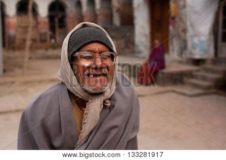 AYODHYA, INDIA - JAN 27, 2103: Poor elderly man in vintage glasses walks the street on January 27, 2013 in India. 60-plus age group in India will increase to 100 million people in 2013.
