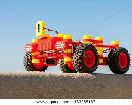 Radio Controlled car assembled from kids construction building kit. Produced by 3d printing from termoplastic filament. Red yellow electric robot on blue sky background. Soft focus. Focus on the nearest headlight. Educational toy. Battery and servers.