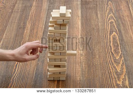 Close-up hands of man playing with wooden blocks. Full concentration. Entertainment activity. Education and development. Game of physical and mental skill. Removing blocks from a tower. Keeping balance.