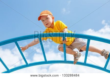 little boy is afraid of heights. Fear of heights. cautious child climbs up the ladder on the playground. copy space for your text