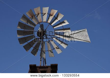 Windmill turns in the blue springtime skies of Texas