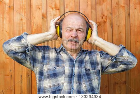 Elderly Man In A Protective Building Headphones. Unpleasant Sounds During Construction