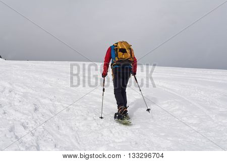 Rear view of unidentifiable cross country snowshoe trekker traveling upward on mountain into dark gray storm clouds