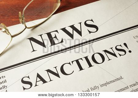 Newspaper with word news and sanctions concept.