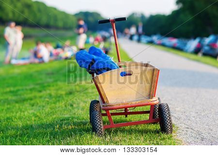 handcart for picnic standing at a meadow with people having a picnic in the blurred background
