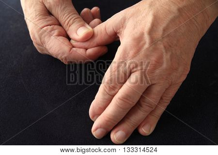Older man has an aching thumb on a black background.