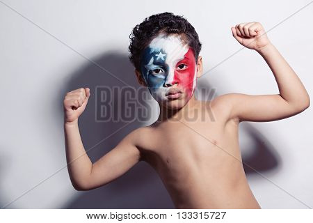 Adorable, mixed race boy, wearing red, white and blue face paint and showing off his muscles.