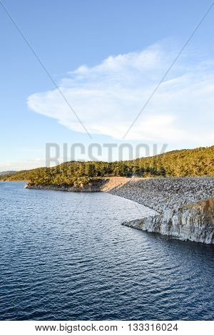 Lake Jindabyne Dam on the Snowy River - in the shadows of the surrounding mountain ranges.  A car is traveling over the dam wall. Lake Jindabyne is part of the ground breaking 'Snowy Mountains Hydro-Electric Scheme' diverting water from the Snowy River to
