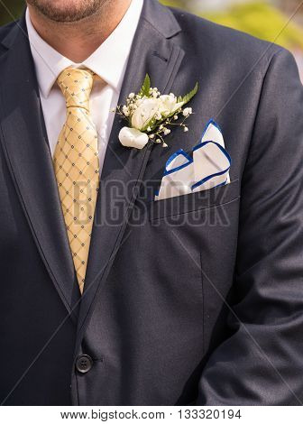 A torso of a man in suit with corsage.