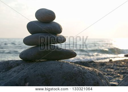 Stones pyramid on beach symbolizing zen harmony balance at sunset over the ocean