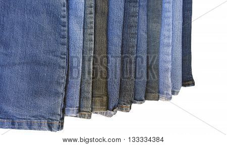 Worn denim jean pant legs in various shades of blue, faded jeans isolated on a white background.