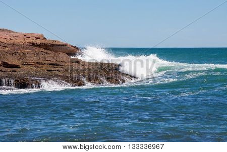 Turquoise waves from the Indian Ocean seascape rushing the sandstone rock outcropping at Pot Alley on a clear day in Kalbarri, Western Australia.